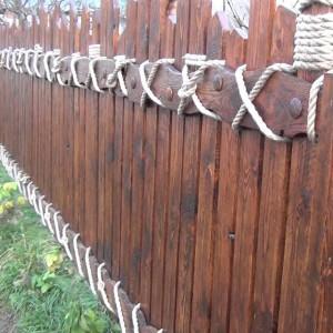 Деревянный забор с вертикальными штакетинами и канатным переплетением